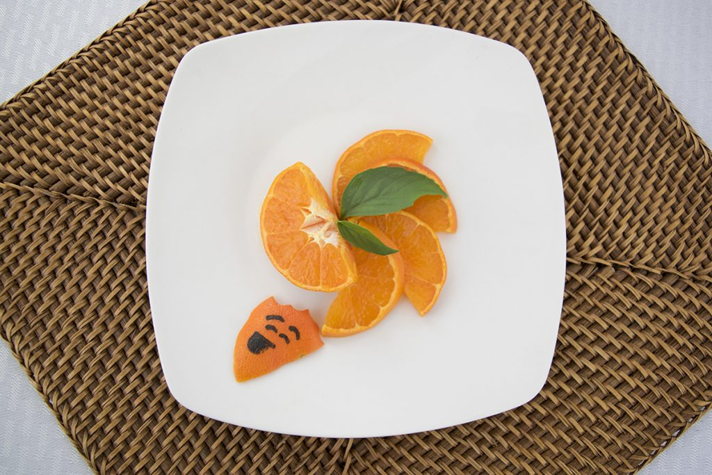 A dismembered orange on a plate