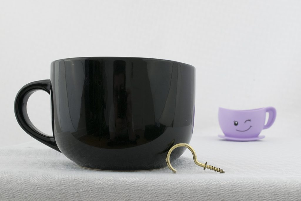 Two coffee cups and a brass hook