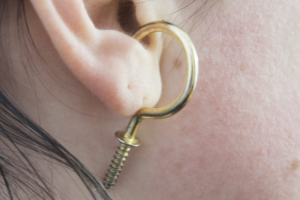 A brass hook hanging off of an ear